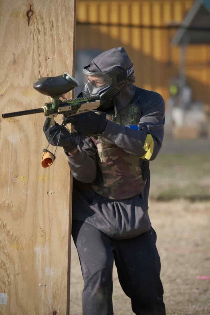 paintball player shooting from behind wood wall